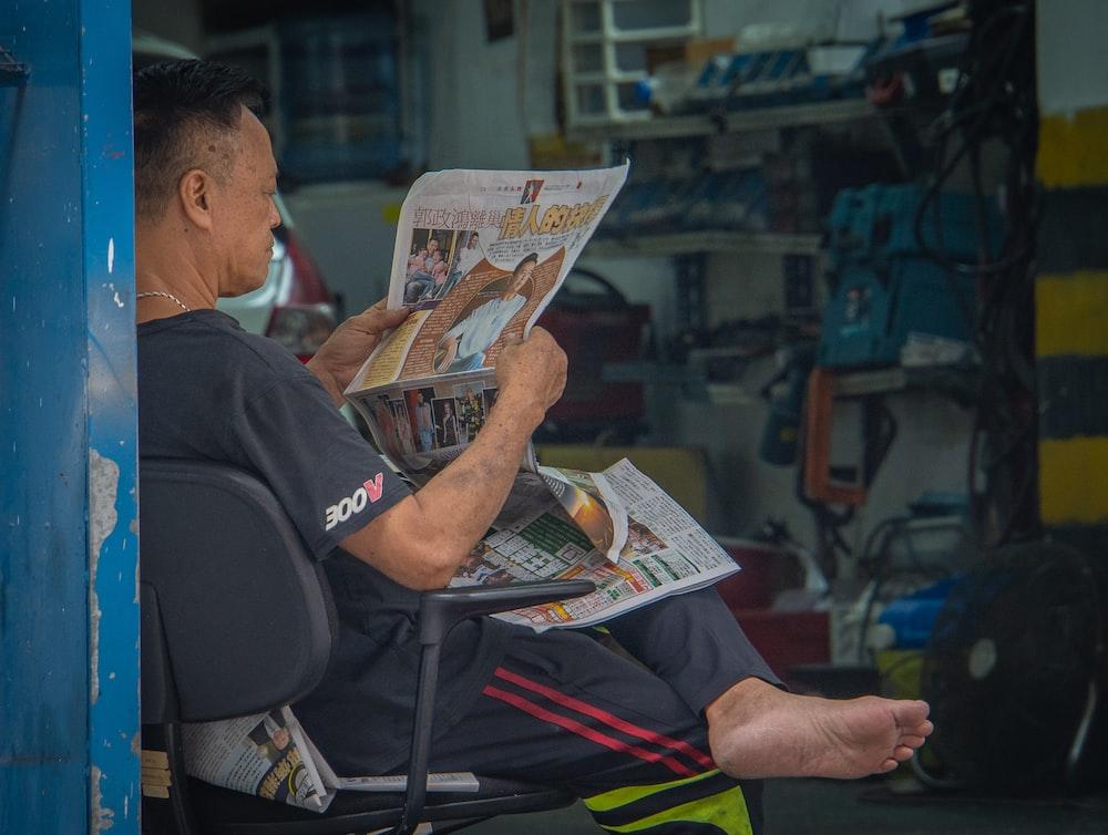 man wearing black shirt sitting on chair reading newspaper