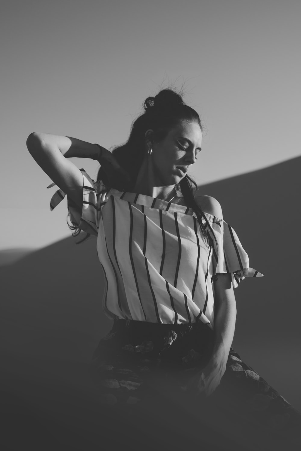 greyscale photo of woman wearing off-shoulder shirt
