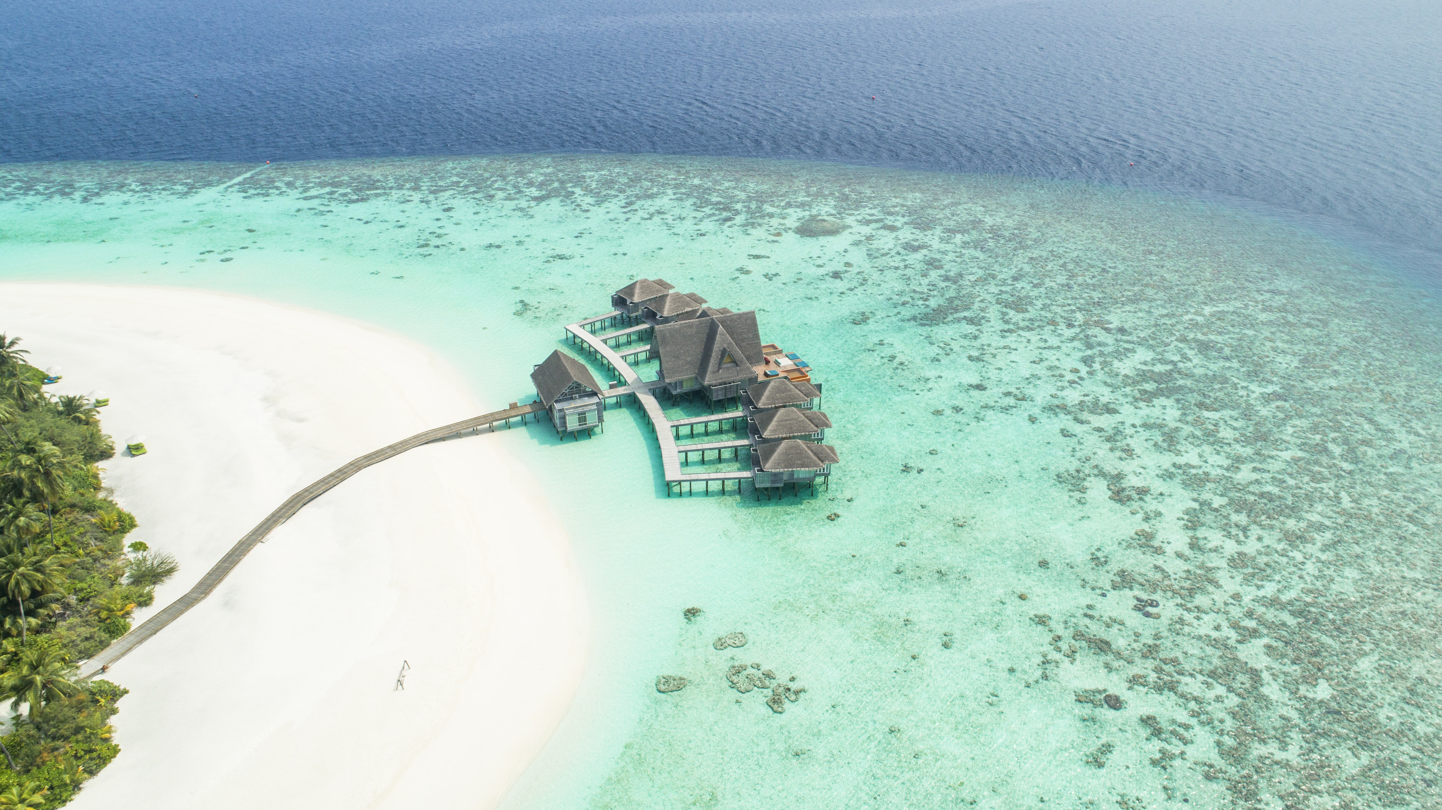 Stunning resort on a pristine island in the Maldives surrounded by coral reefs and ocean