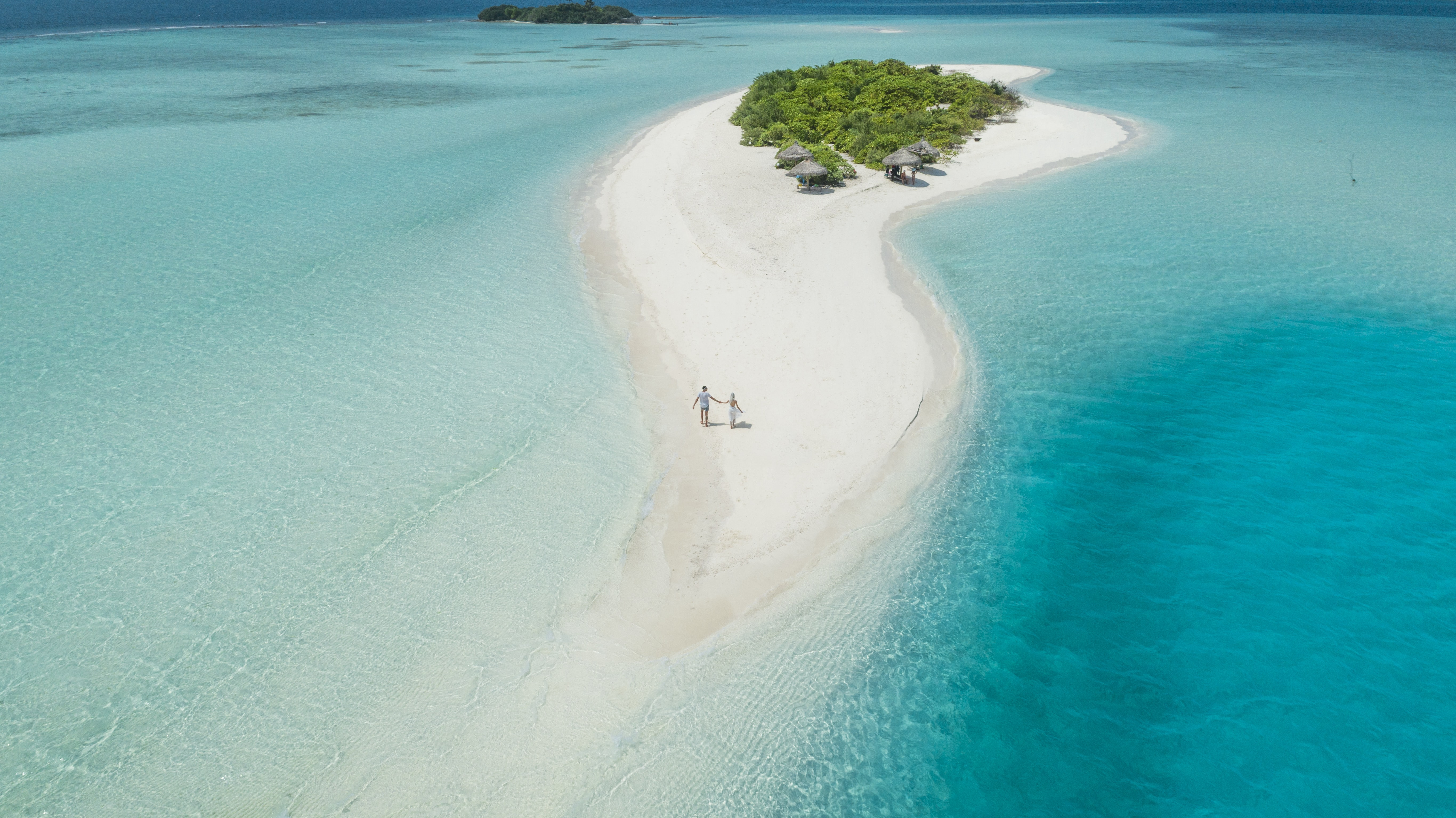 A couple walks hand-in-hand on a beautiful deserted beach in the Maldives