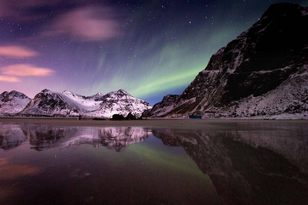 lake beside mountain covered with snow under aurora borealis