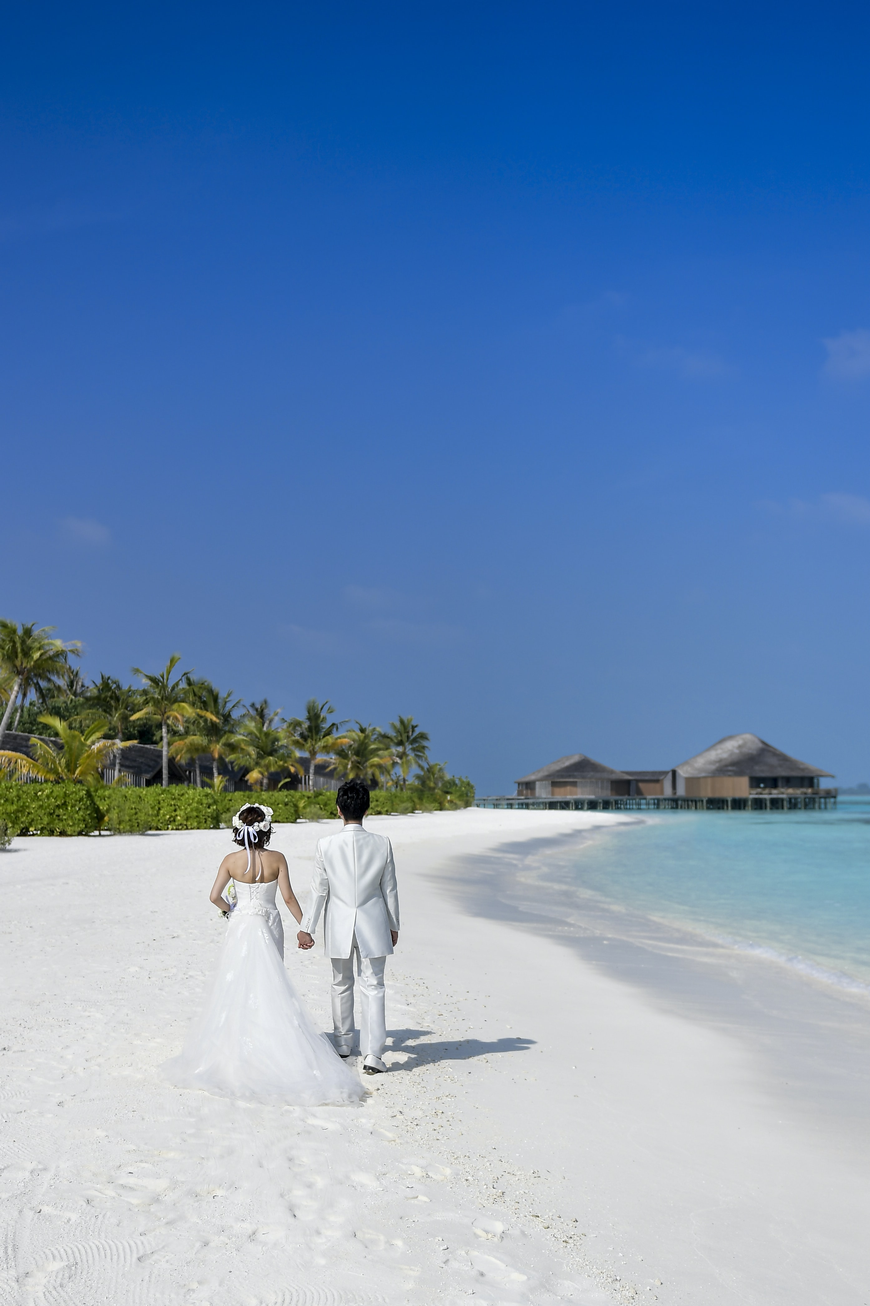A newly married couple walks along a pristine beach in the Maldives