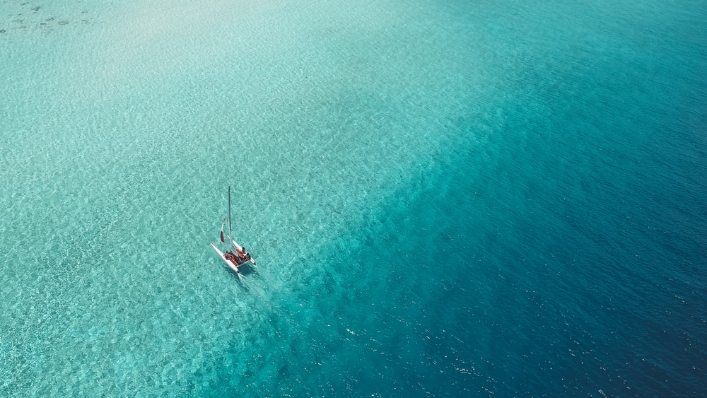 A Catamaran Sails Across A Shallow Reef In The Maldives