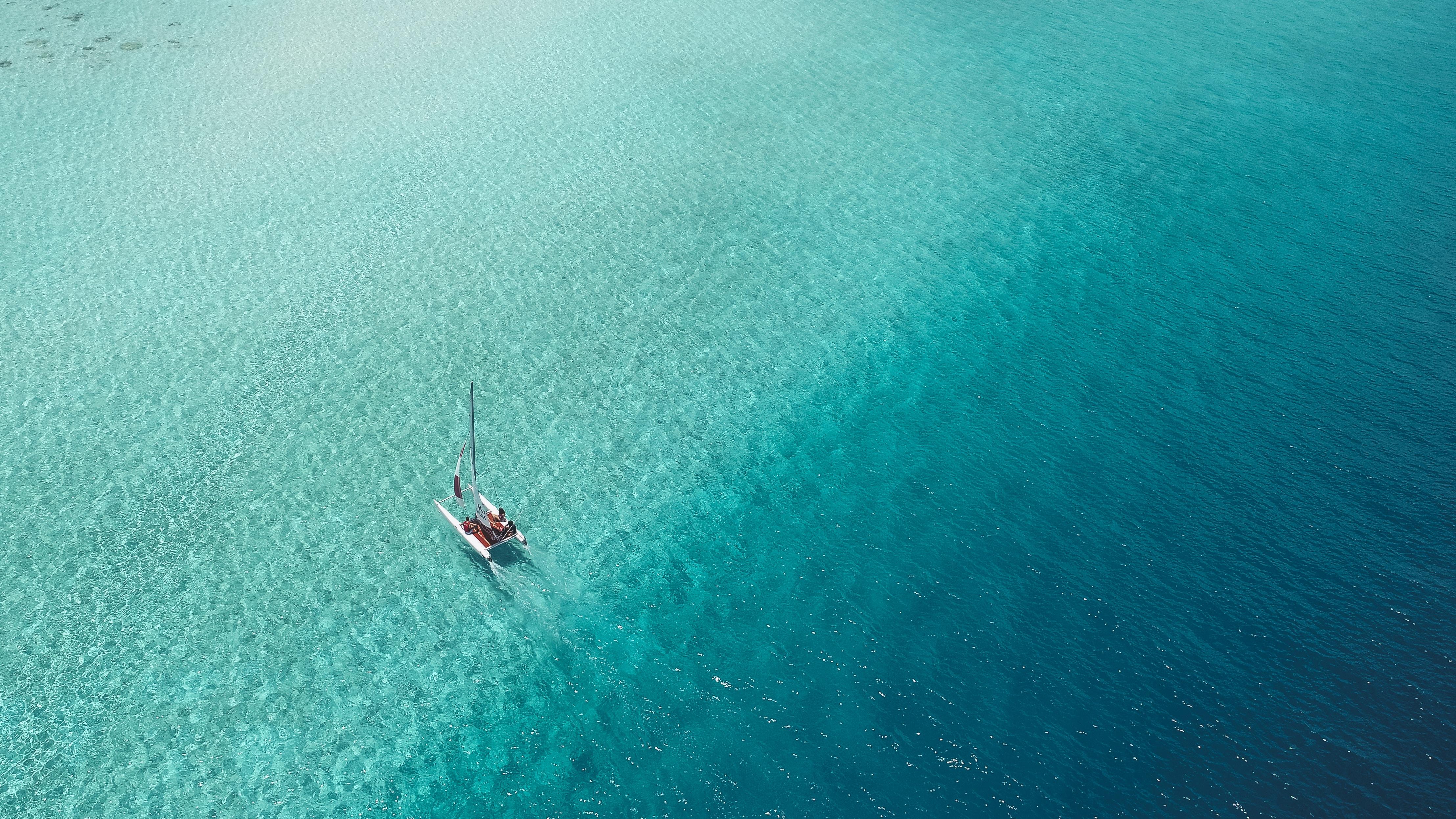 A catamaran sails across a shallow reef in the Maldives