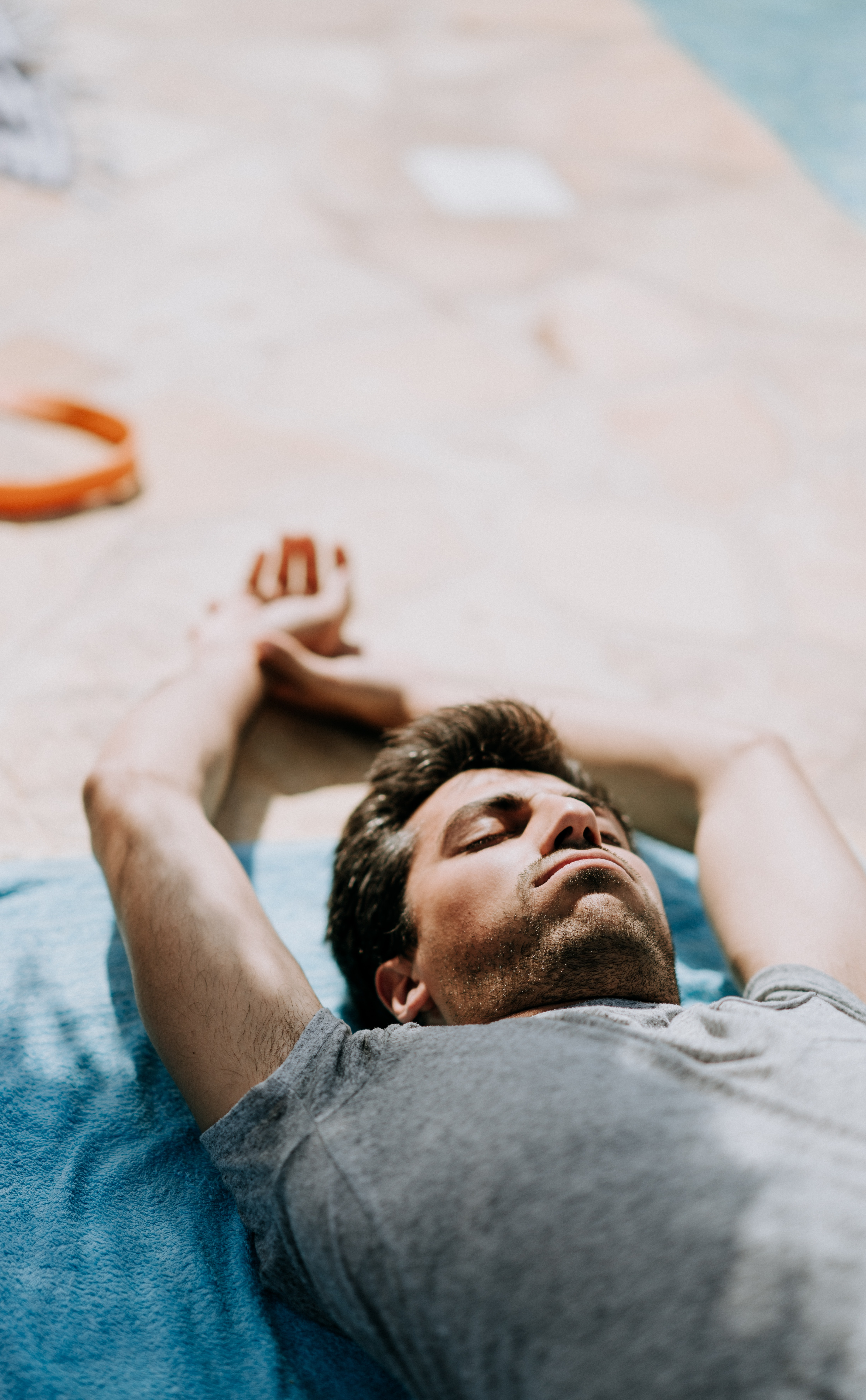 selective focus photography of man lying on blue cushion during daytime