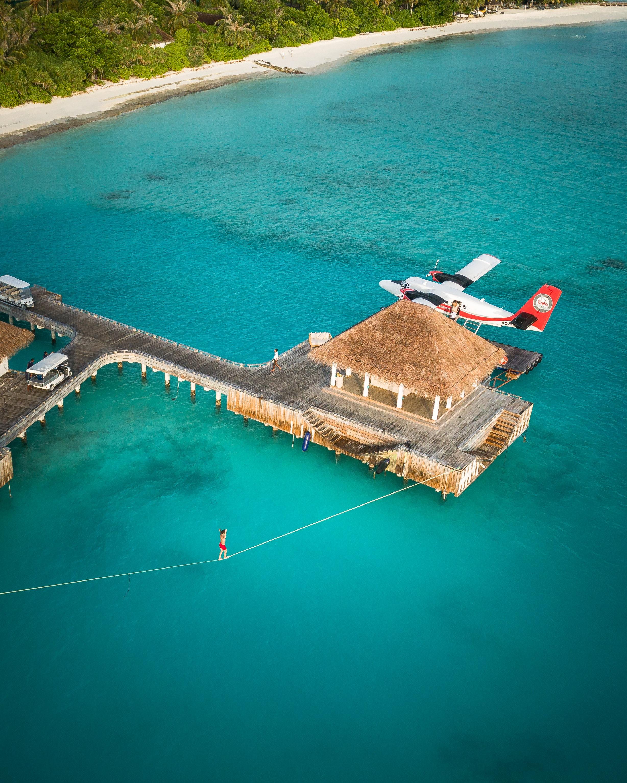 Man slacklines across his resort villa in the Maldives next to a sea plane