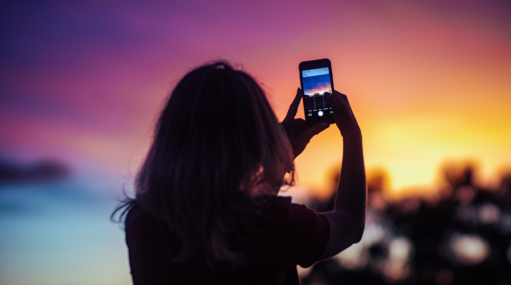 woman taking photo of sunset