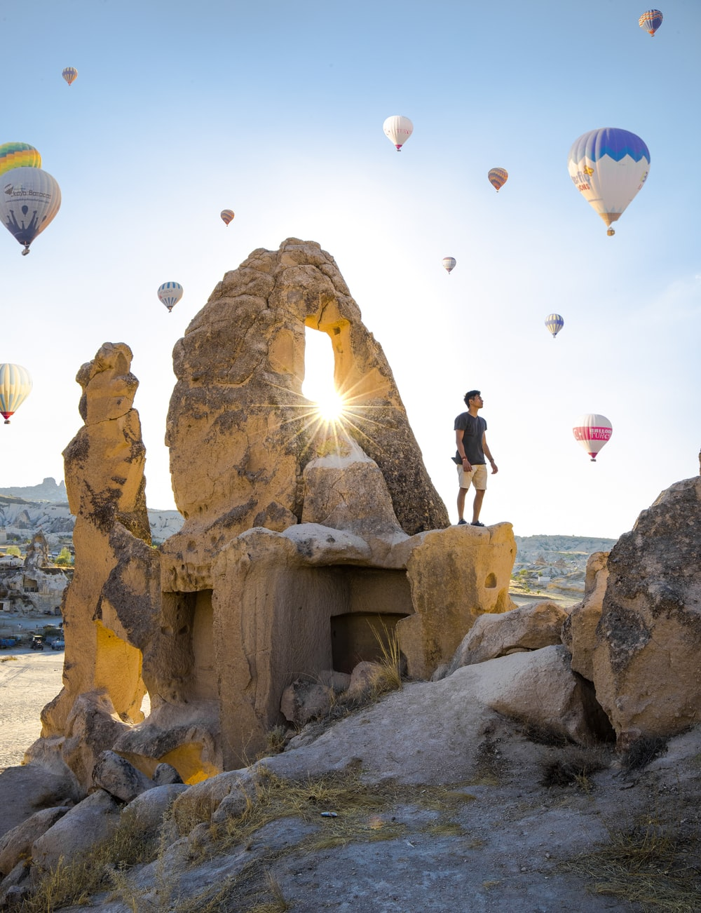 man standing on rocky hill and assorted-colored hit air balloons on skies