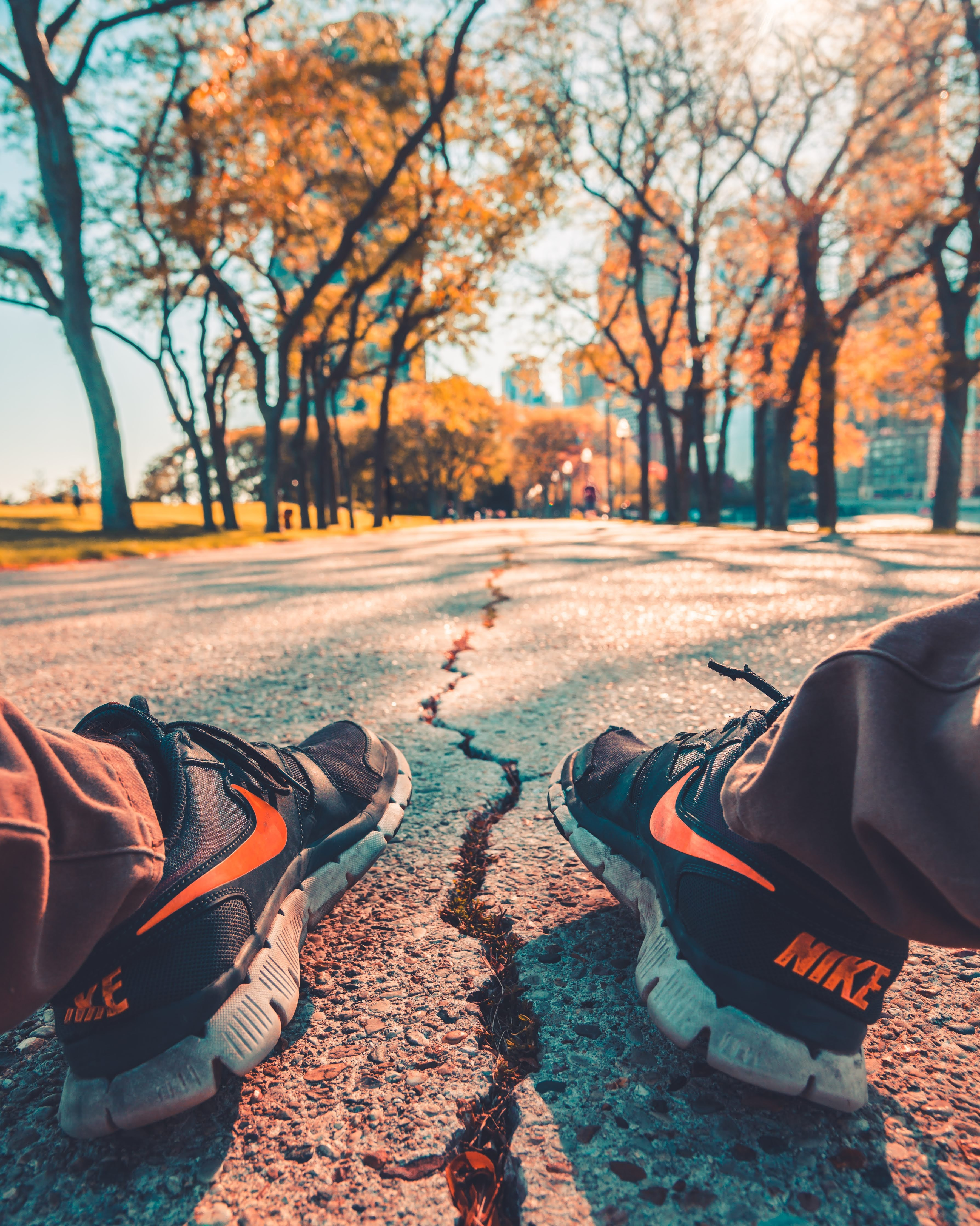 person wearing Nike running shoes sitting on road outdoor