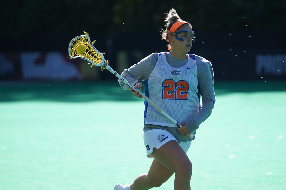 woman lacrosse player running on field at daytime