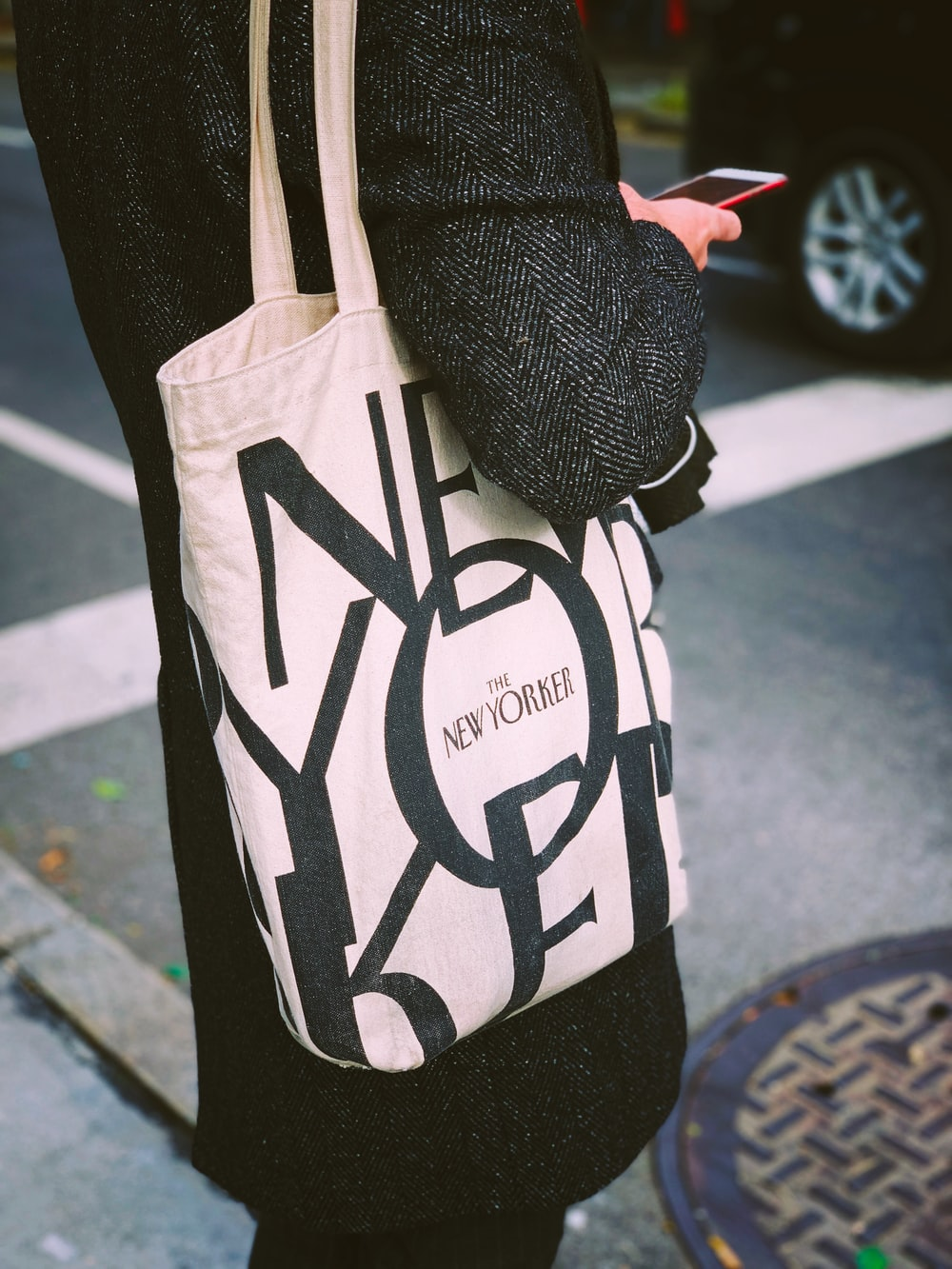 person carrying white and black tote bag