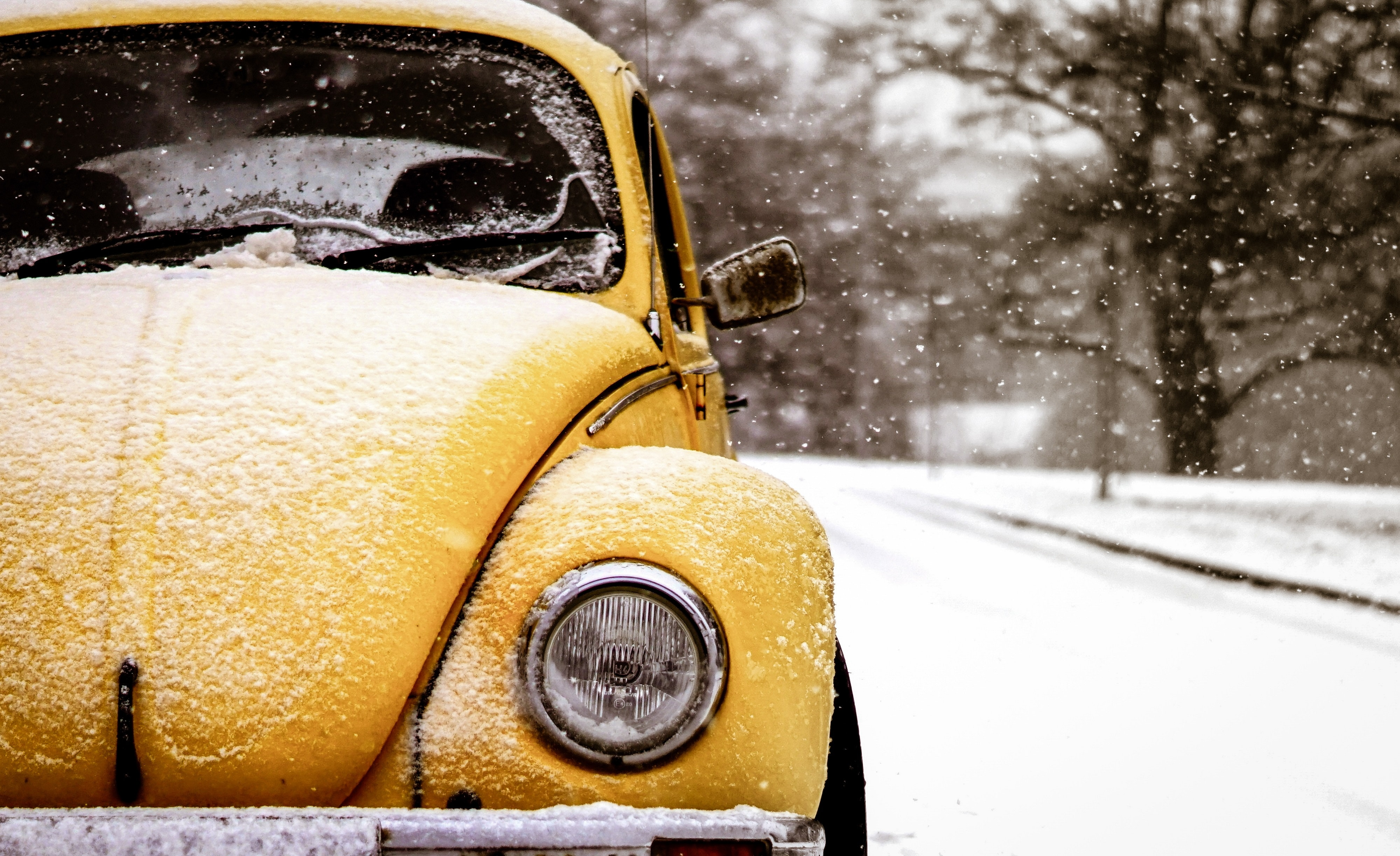 yellow Volkswagen Beetle on road covered by snw