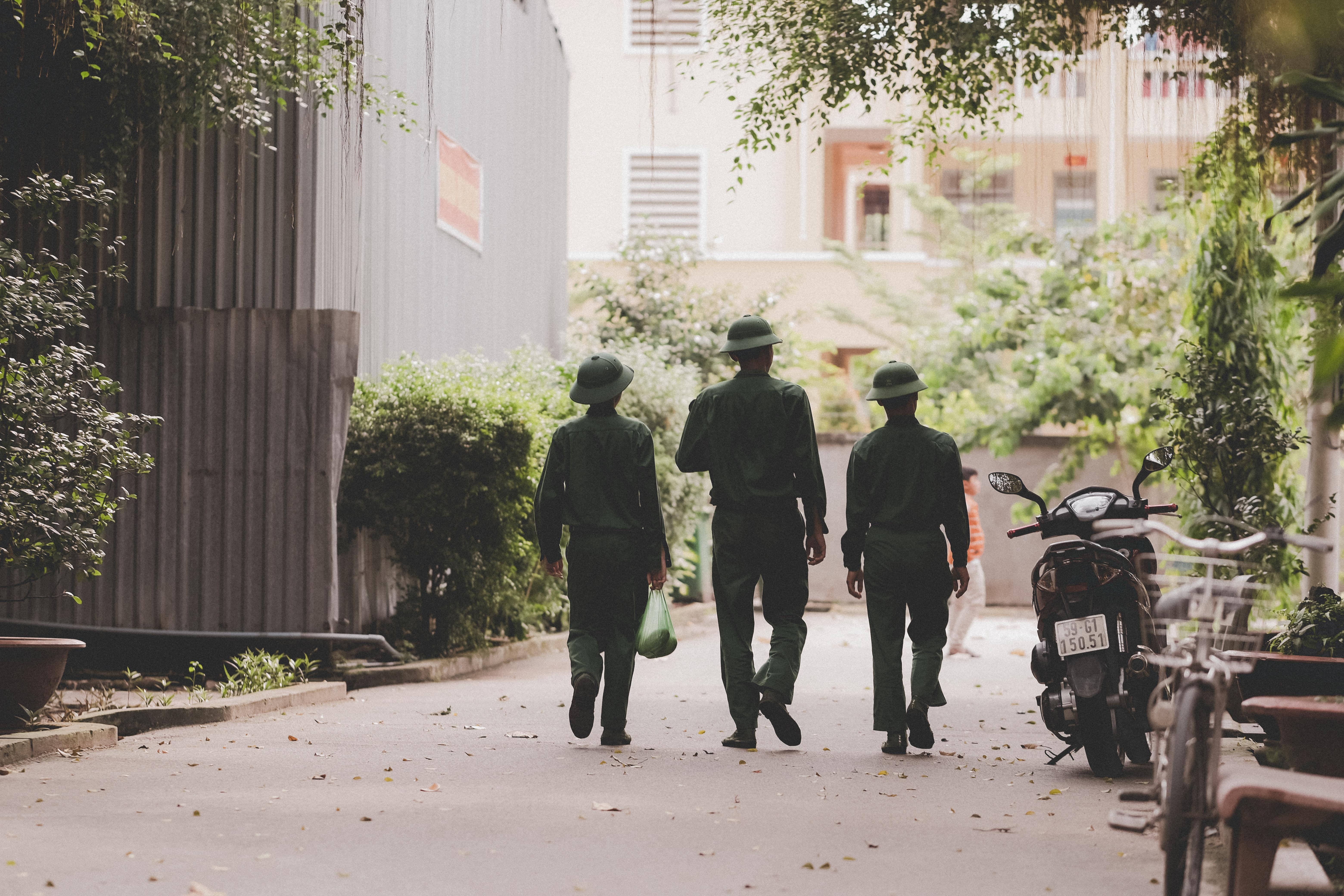 three men walking beside black motorcycle during daytime