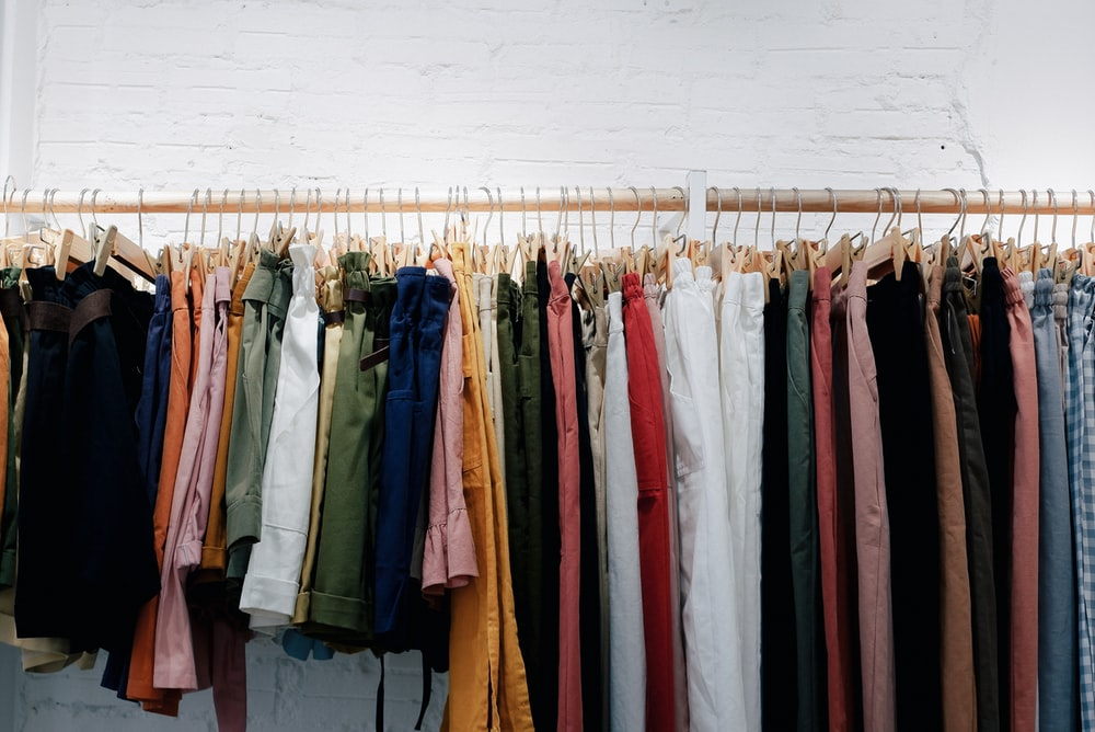 assorted-color clothes lot hanging on wooden wall rack