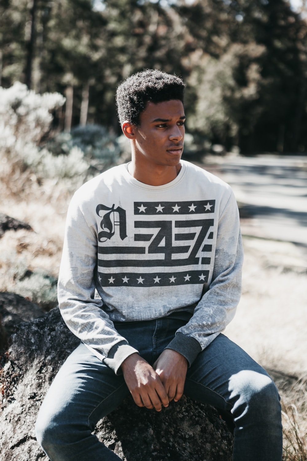 man in gray sweater sits on rock while looking into left