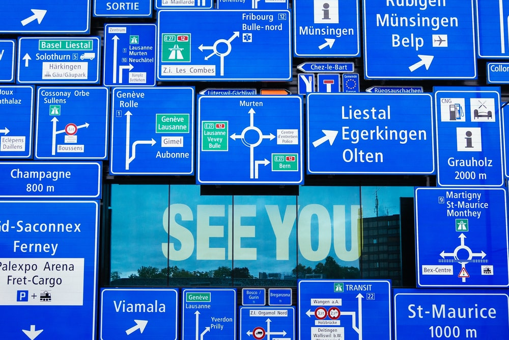 See You displayed on glass window with blue road signage hanging outside the window
