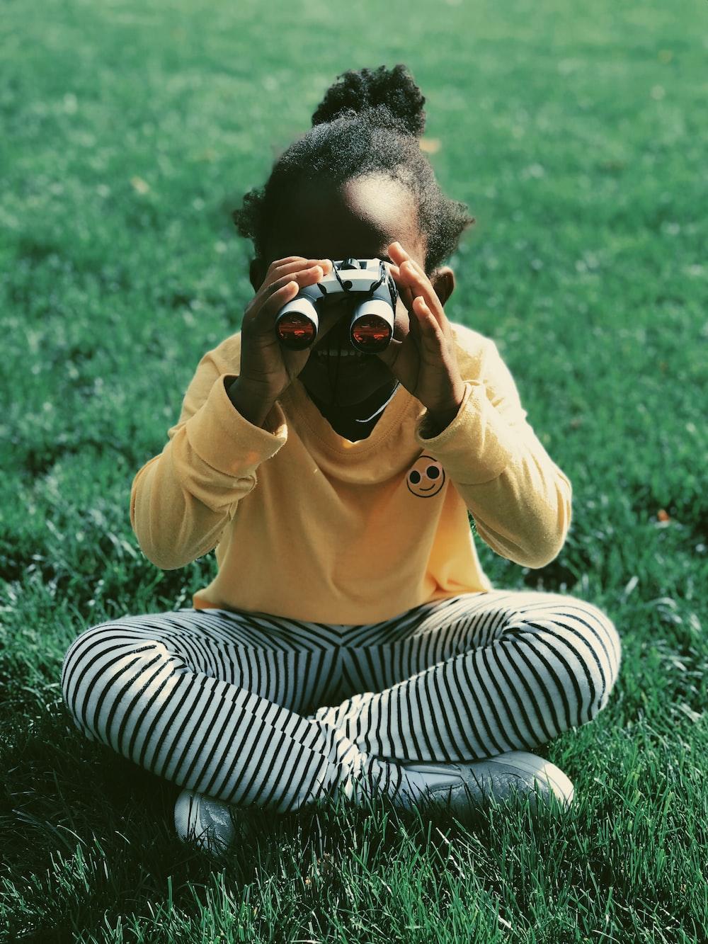 girl sitting on grass field holding binoculars