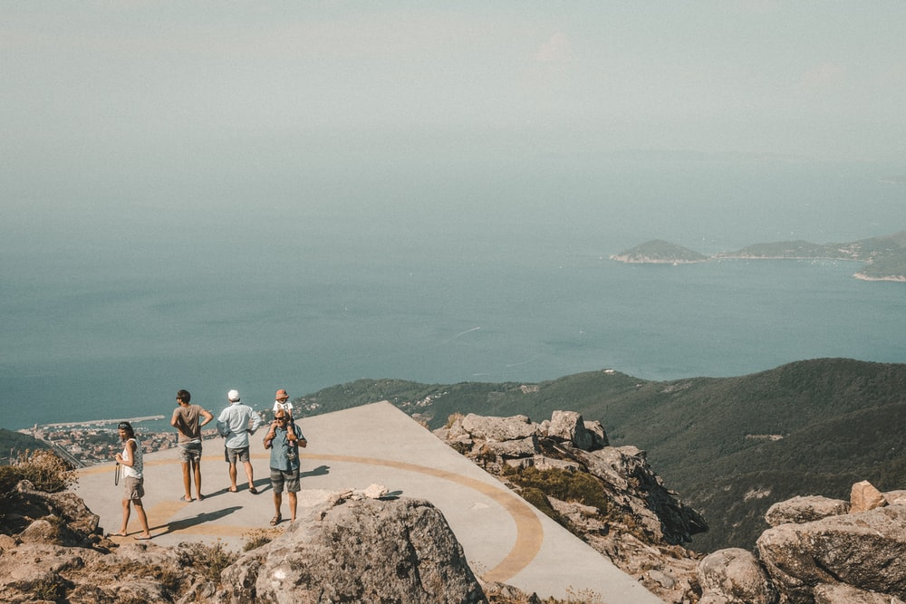 peoples standing on mountain