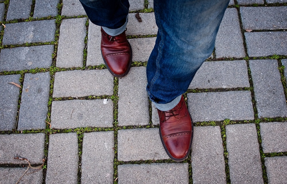 man wearing leather shoes walking on paved pathway