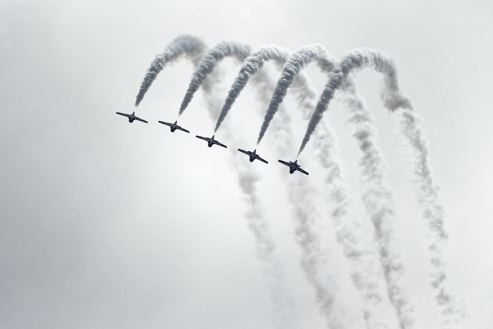 five jet planes in grayscale photography