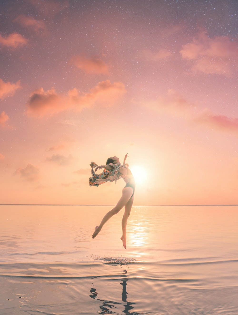 woman jumping on body of water