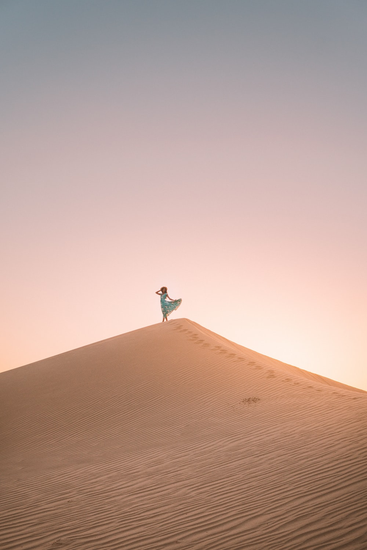 woman standing on desert hill