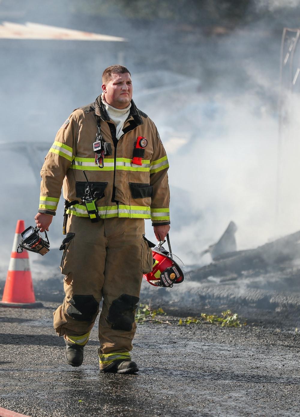 fireman holding helmet standing on road