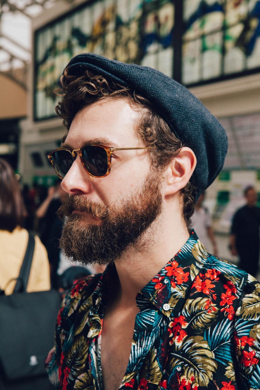 man wearing multicolored floral shirt and black framed black lens sunglasses