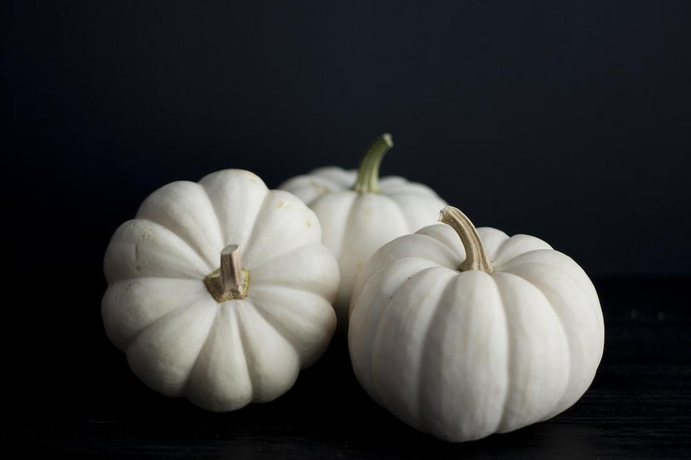 three white squash on black background