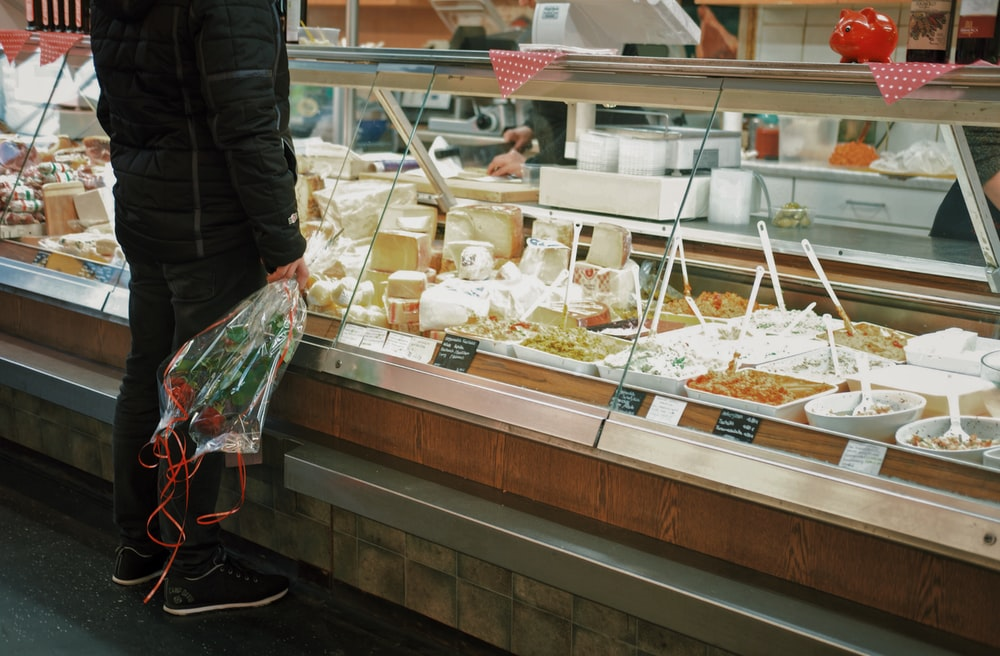 man with bouquet of roses standing in front of food display