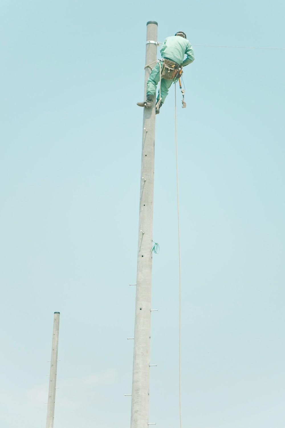 man in blue suit on top of the electic post