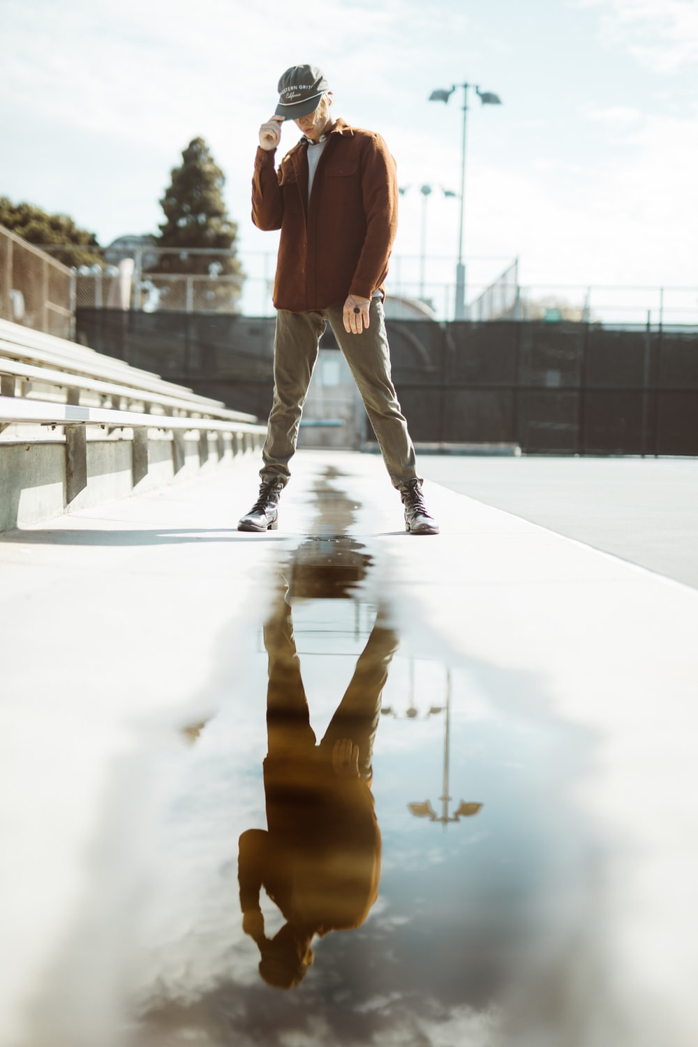 man standing on road with water reflection during daytime