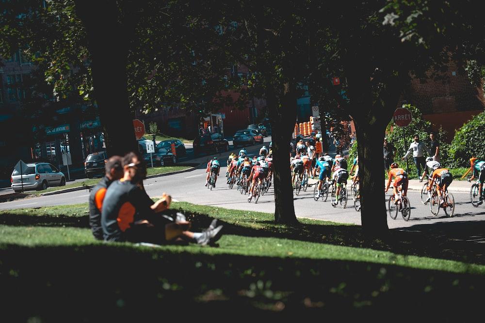 men sitting on grass field near trees and street with men in bike marathon