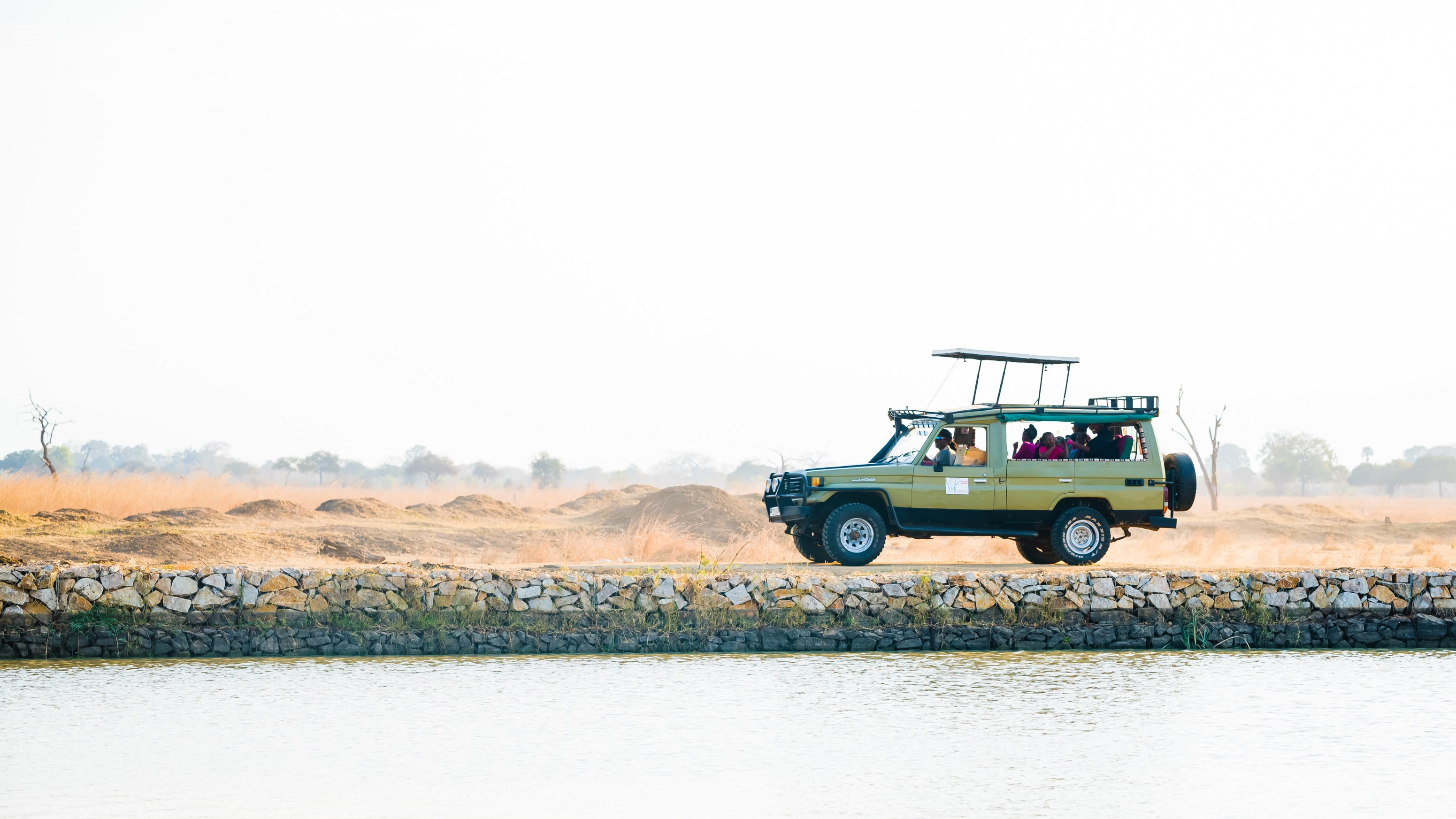 gray SUV near body of water under clear sky