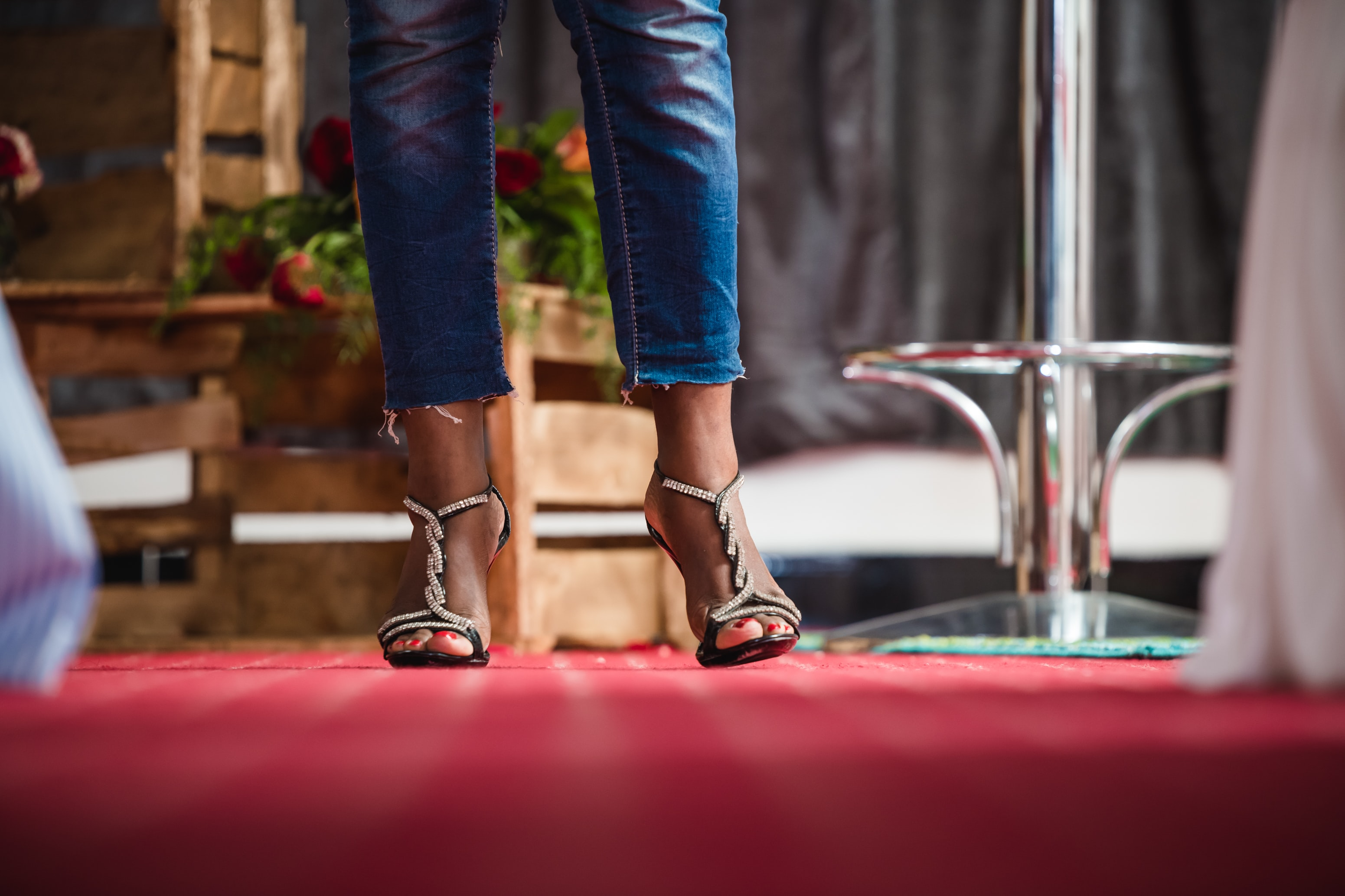 woman wearing blue denim pants and brown heeled sandals standing besides gray stainless steel bar chair
