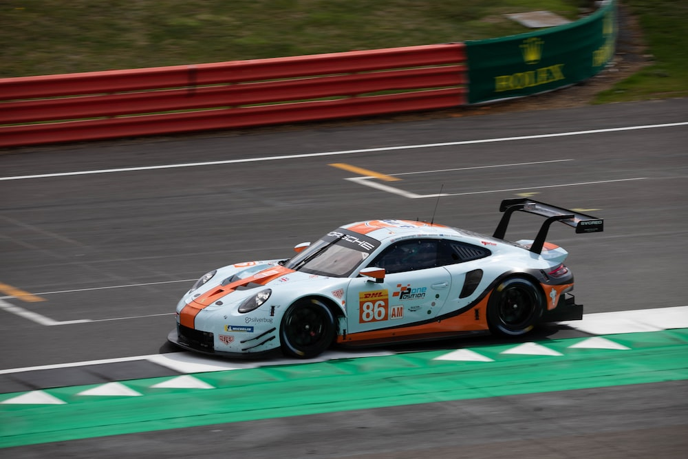 white and orange racing car on road