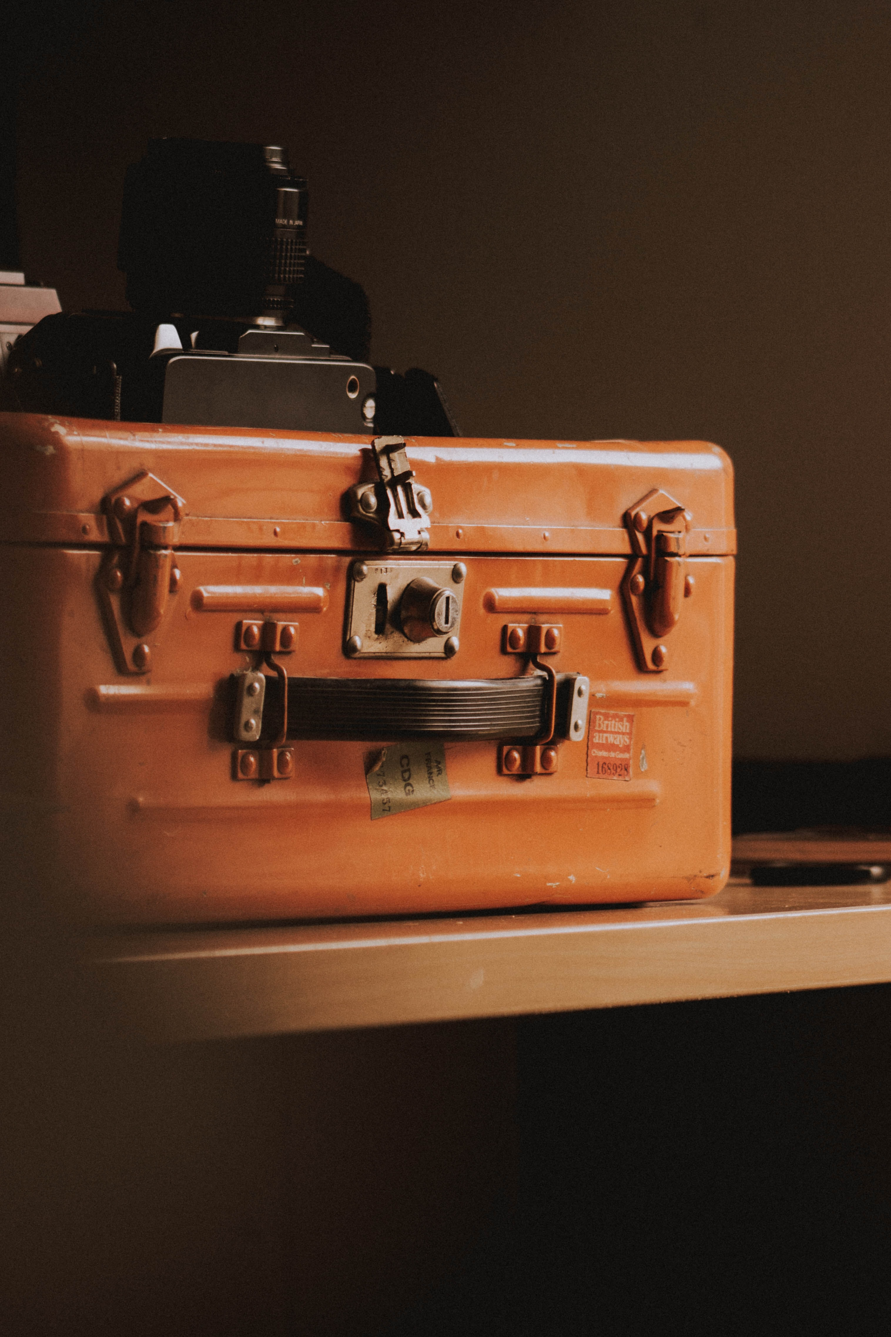 brown suitcase on top of table