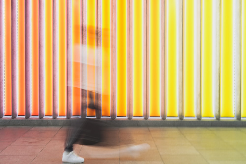 person walking in front of yellow and white light