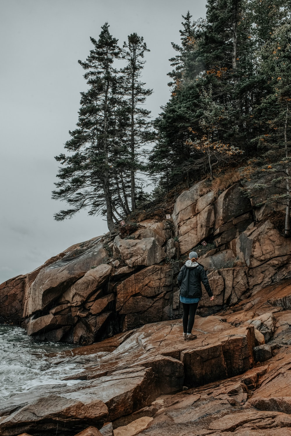 person stands on rock beside body of water