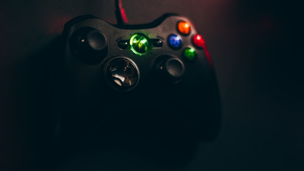 black Xbox 360 corded game controller on black surface