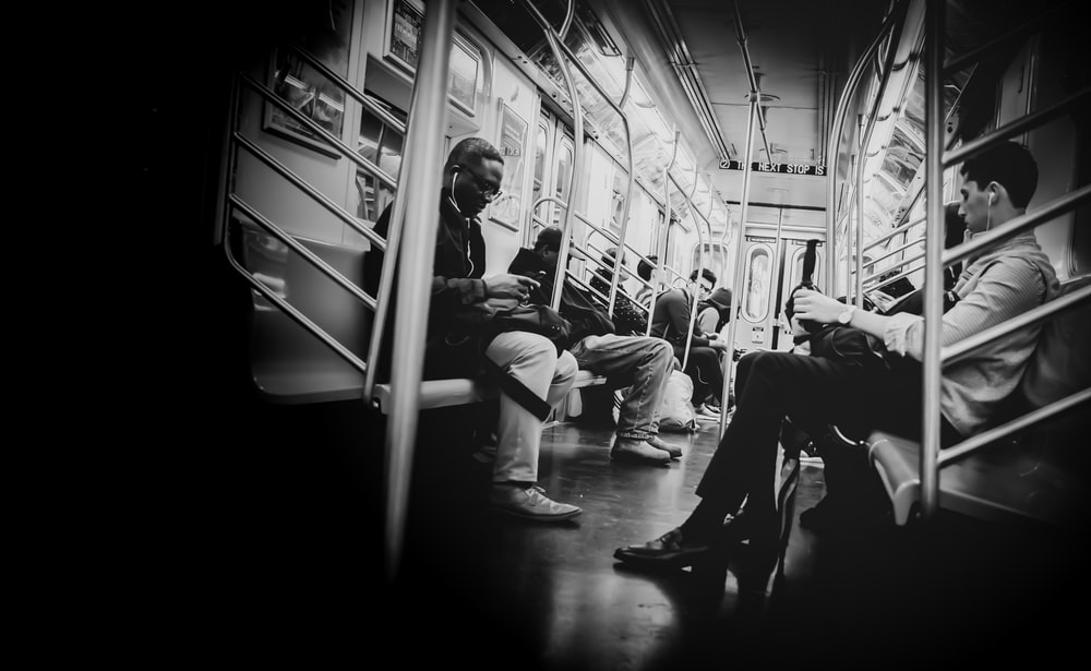 grayscale photography of people sitting inside train