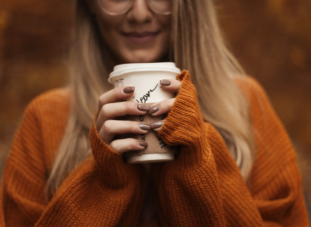 smiling woman standing and holding coffee cup with lid