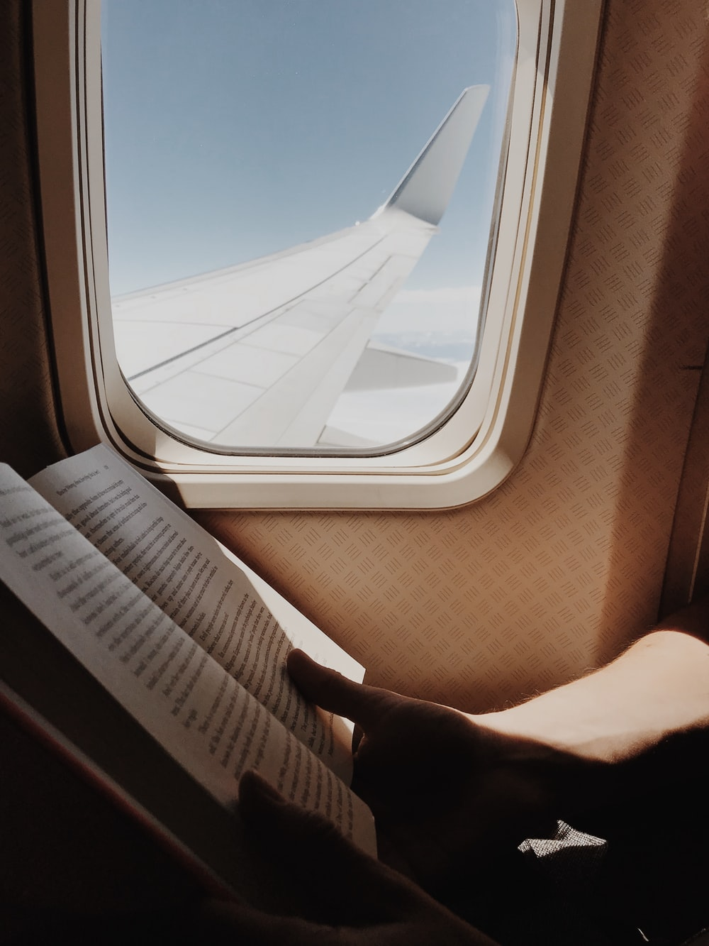 person reading book beside airplane window