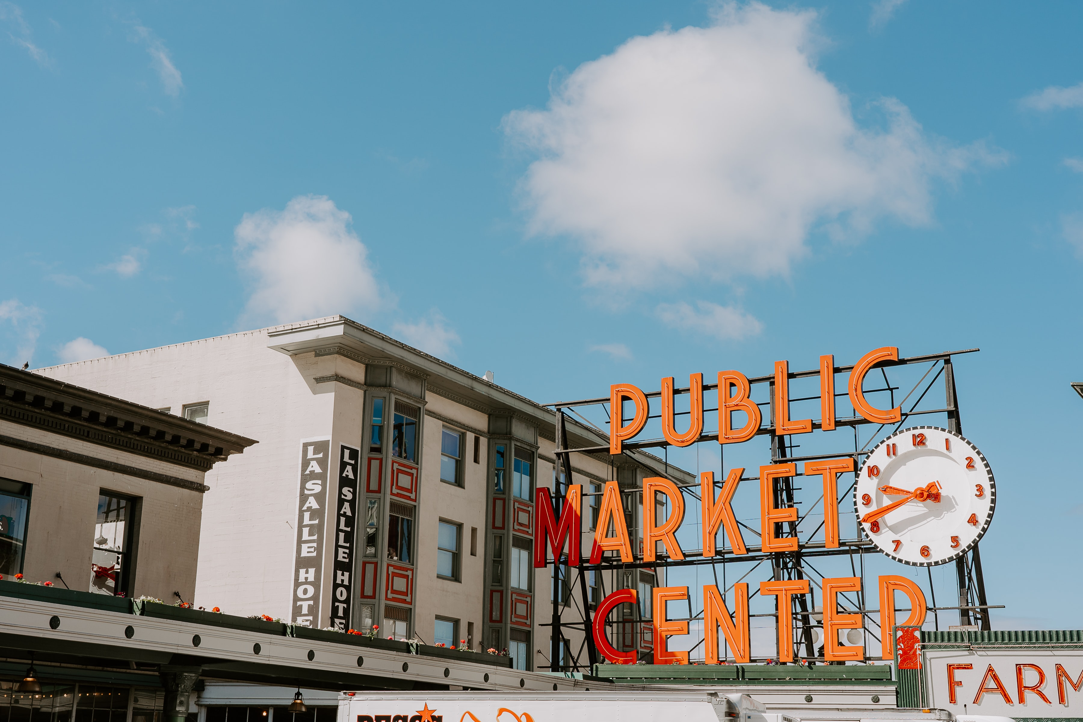 public market center neon light near white painted building