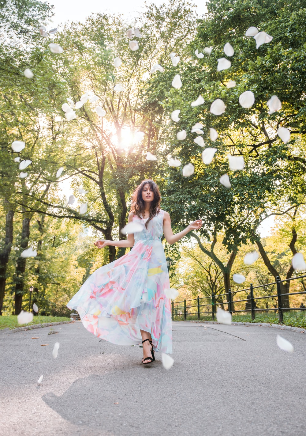 woman in floral maxi dress walking on street between trees