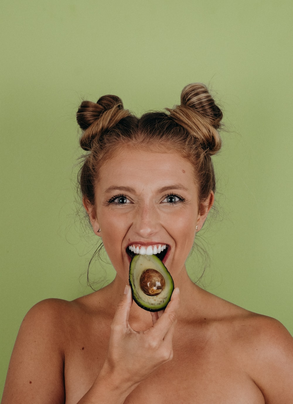 woman holding sliced avocado