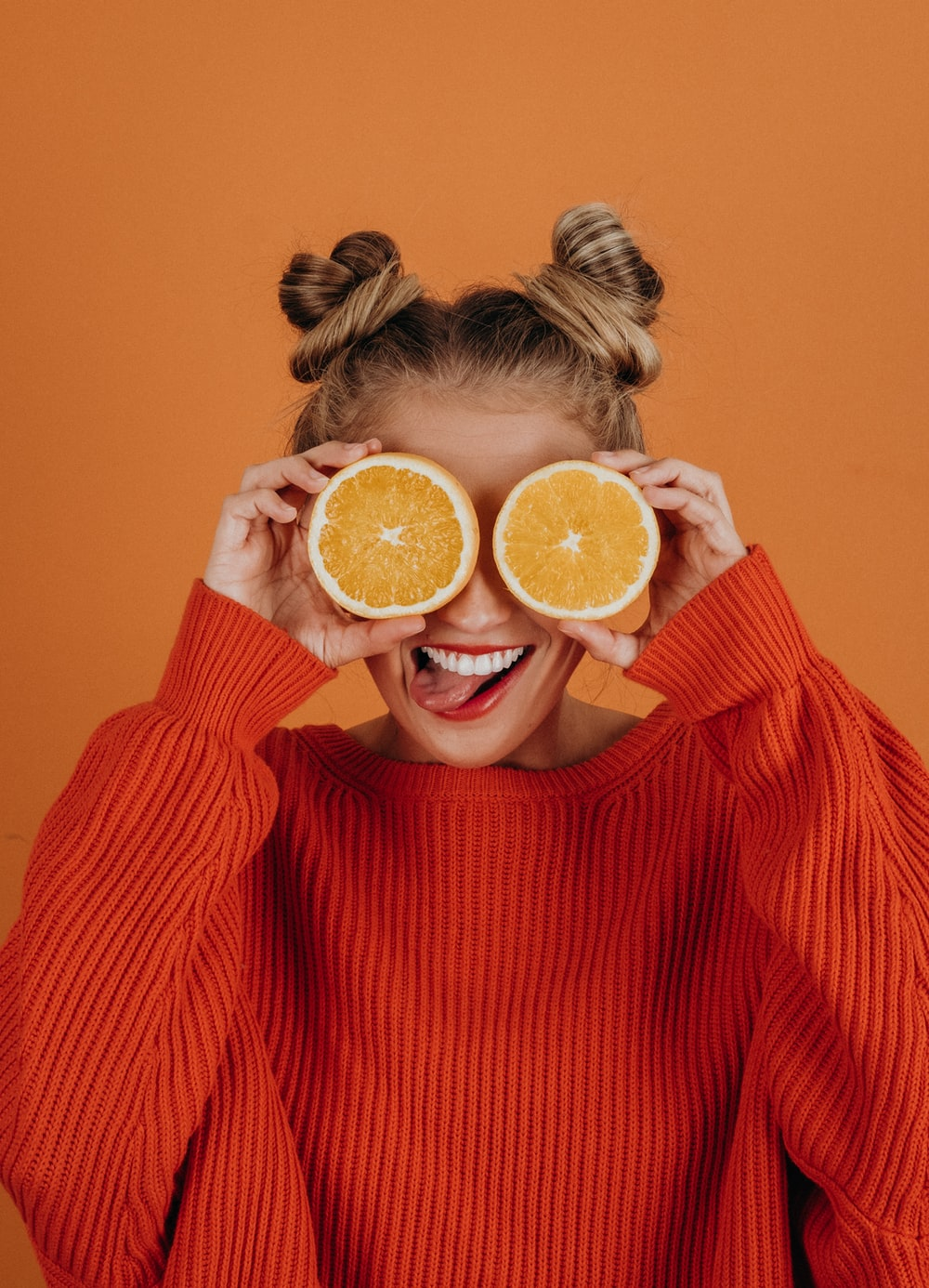 woman in red knit sweater holding lemon