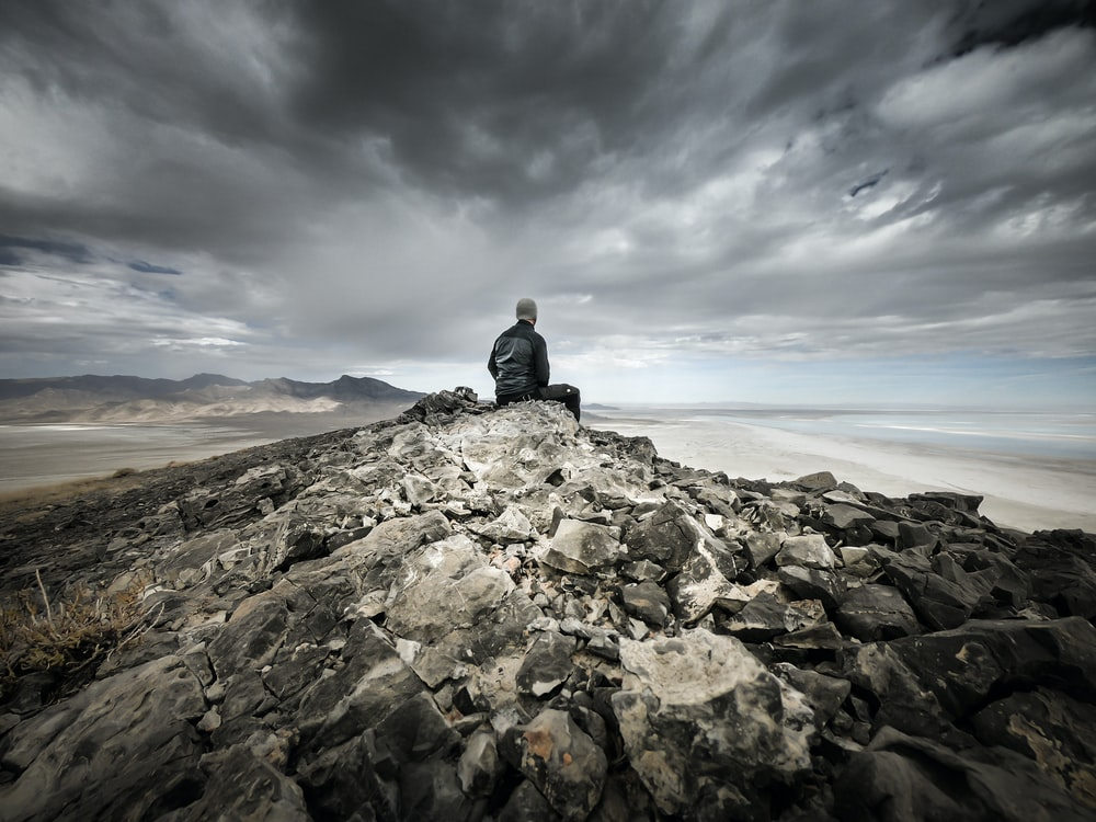 man siting on gray rocky mountain