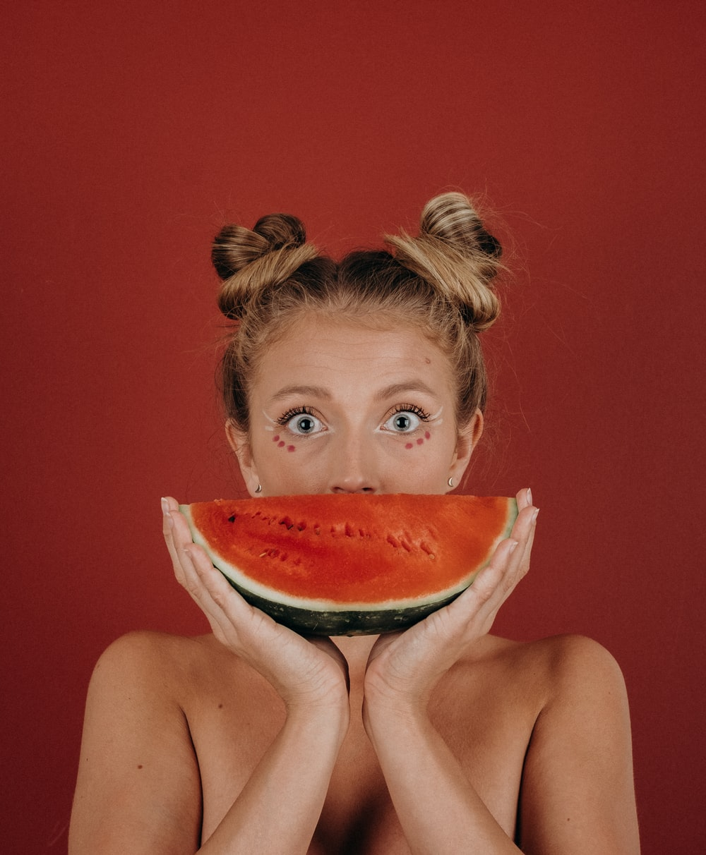 woman covering her mouth with watermelon