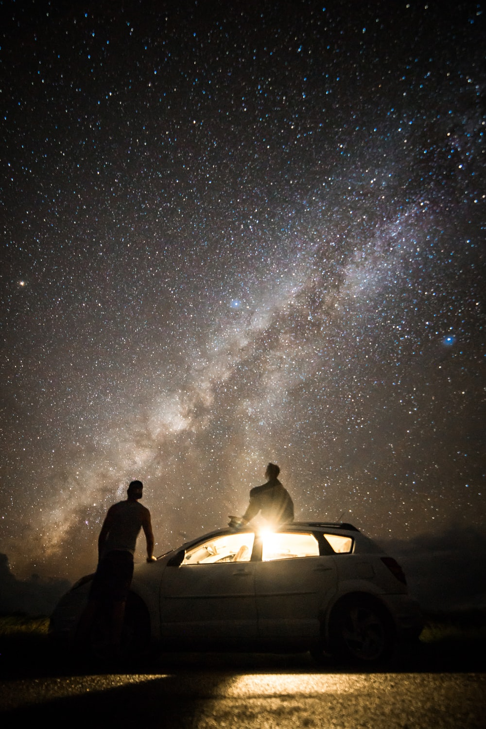 man sitting on the roof of the car watching the stars